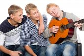 Friends spend leisure time playing the guitar. Two of the boys twin brothers.