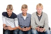 Young guys use smartphones and sitting on the couch. Two of the boys twin brothers.