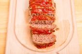 stock photo of meatloaf  - A fresh baked meatloaf sliced on a wood cutting board - JPG
