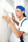 painter worker peeling off wallpaper from wall during interior home repair renovation work