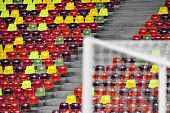 image of tribunal  - Detail with empty colored sports arena tribunes on a football stadium