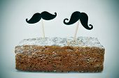 two different moustaches stuck in a piece of cake