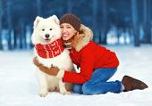 Christmas, Winter And People Concept - Happy Pretty Woman Having Fun With White Samoyed Dog Outdoors