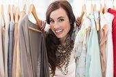 Pretty brunette smiling at camera by clothes rail at clothes store