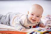 Happy gurgling baby lying on his bed playing with colorful pictures in a book looking at the camera with an adorable beaming smile of contentment