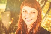 Beautiful freckle Woman With Red Hair In Fall Park