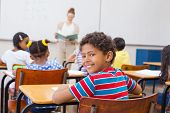 picture of pupils  - Cute pupil smiling at camera in classroom at the elementary school - JPG