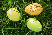 image of pasqua  - feliz pasqua against three easter eggs wrapped in foil - JPG