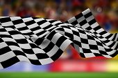 image of football pitch  - Checkered flag against blurry football pitch with crowd - JPG