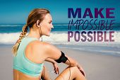 foto of impossible  - Fit woman sitting on the beach taking a break smiling against make impossible possible - JPG