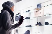 foto of boutique  - Casualy winter dressed lady window shopping in front of sinfully expensive boutique store dispaly window - JPG