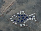 Fish shaped mosaic crammed in the pavement