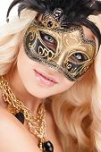 stock photo of mystery  - Beautiful young woman in a mysterious gold Venetian mask - JPG