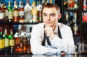 stock photo of bartender  - Portrait of young barman worker at bartender desk in restaurant bar  - JPG
