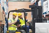 picture of forklift driver  - Warehouse worker talking with forklift driver in warehouse - JPG