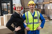 stock photo of warehouse  - Warehouse worker and his manager with hands on hips in a large warehouse - JPG
