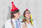 picture of party hats  - Geeky hipster wearing a party hat with blowing party horn against white background - JPG