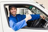 pic of shipping receiving  - Delivery driver smiling at camera in his van outside the warehouse - JPG