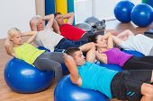 foto of bending over backwards  - Determined people stretching on exercise balls in fitness club - JPG