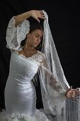 stock photo of cross-dress  - Flamenco dancer backs with white dress and hands crossed up on black background - JPG