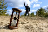 stock photo of hourglass figure  - Hourglass on sand against man silhouette in pine forest - JPG