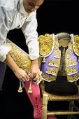 pic of bullfighting  - Woman bullfighter by dressing with vest on a black background  - JPG