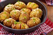 stock photo of green onion  - Baked hasselback potatoes with cheese and green onion - JPG