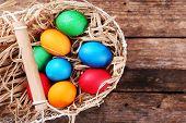 picture of wooden basket  - Easter eggs in basket on vintage wooden planks background - JPG