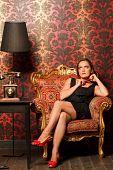 mujer de negro vestido sentado en una silla vintage y que busca sostener un granos rojos