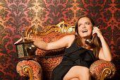 mujer en vestido negro sentado en una silla vintage y hablando por teléfono antiguo