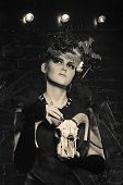 picture of witch  - Halloween witch with an unusual makeup and headdress of bats holding a skull - JPG