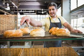 picture of tong  - Smiling waiter taking bread with tongs at the bakery - JPG