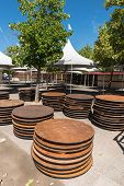 image of canopy  - Canopy tent set up outdoors with many round tables stacked nearby - JPG