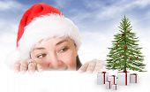 image of christmas hat  - female santa looking at her gifts by the christmas tree  - JPG