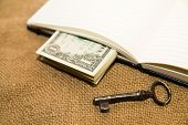 pic of memento  - Opened notebook with a blank sheet key and money on the old tissue - JPG
