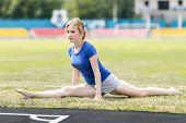 pic of do splits  - Fit sporty woman  doing stretching exercises - JPG
