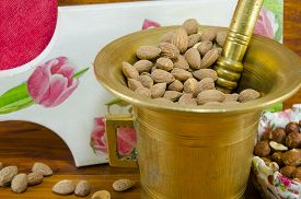 stock photo of decoupage  - Hazelnuts in a old mortar with an decoupage decorated tray in background on a table with nuts and almonds in a bowl - JPG
