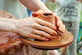 foto of loamy  - Potter hands taken closeup on pottery wheel clay pot - JPG