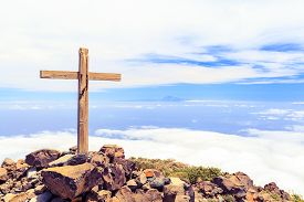 image of christianity  - Christian wooden cross on mountain top rocky summit beautiful inspirational landscape with ocean island clouds and blue sky looking at scenic blue sea and white clouds - JPG