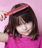 Cute little girl reluctantly brushing her hair