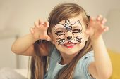 Portrait of funny girl with face painting on blurred background poster