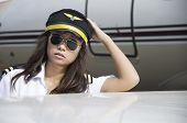 Beautiful female pilot are steward beside aircraft