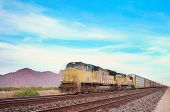 image of chug  - Cargo locomotive railroad engine crossing Arizona desert wilderness during sunset - JPG