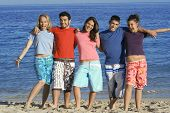 Five friends in different coloured t-shirts,goofing about at beach