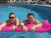 Young couple on pink airbed posing in swimming pool