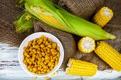 Ripe Yellow Corn And Canned Corn In A White Bowl On A Wooden Table. Yellow Ripe Corn, Top View poster
