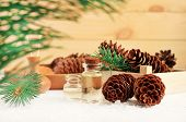 Bottles With Essential Aroma Oil With Pine Cones And Green Fir Tree Branches, Wooden Background. Win poster
