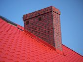 Closeup of red roof metal covering with brick chimney