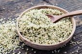 Organic Blanched Hemp Seeds In A Bowl With Spoon On Rustic Wooden Table. Healthy Eating Supplement.  poster