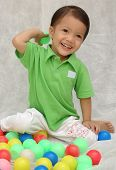 Cheerful little boy playing with balls